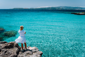 Jung adult women in white dress on summer vacation in front of sea coast landscape of small beach with crystal clear blue azure water (Greece, Kefalonia)