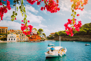 Kefalonia Greece Assos village, fishing boat in tranquil bay and magenta fuchsia blossom. Picturesque colorful houses and pine groves