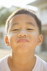 kidding face of asian children standing outdoor