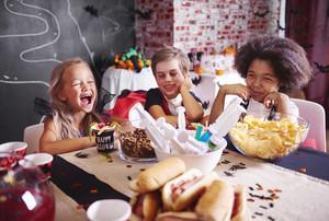 Kids in halloween costumes having a snack