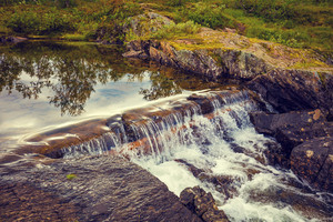 Landscape with little waterfall on a mountain river. Wild nature of Norway