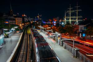 Landungsbruecken in Hamburg during night. Panorama of Harbor and metro station, Germany. Light trails Long exposure