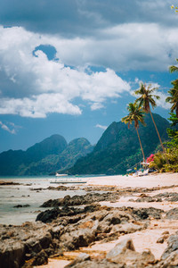 Las Cabanas beach, palm trees, mountain and cloudscape in El Nido, Palawan island, Philippines