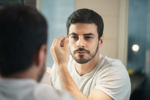 Latino person with beard grooming in bathroom at home for morning routine and body care. White metrosexual man trimming eyebrows with tweezers