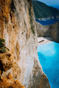 Limestone chalk huge cliff rocks and Navagio beach with abandoned Shipwreck in the distance. Azure blue colored sea. Zakynthos island, Greece