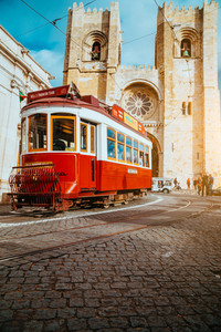 LISBON, PORTUGAL - December 31, 2017: Street view with famous old historic tourist red tram in front of the main Lisbon Cathedral, Portugal