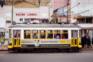 LISBON, PORTUGAL - December 31, 2017: Street view with famous old historic tourist yellow tram. Famous vintage tourist travel attraction. Colorful architecture city buildings street scene, Portugal
