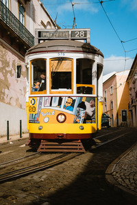 LISBON, PORTUGAL - January 01, 2018: Iconic yellow tram Line 28 in Lisbon, Portugal. Lisbon's tram driving down narrow street on sunny day