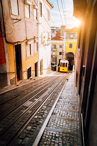 Lisbon's Gloria yellow funicular in sunset beam light. Lisbon, Portugal. West side of the Avenida da Liberdade connects downtown with Bairro Alto.