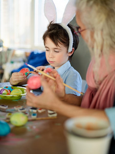 Little boy and his grandmother painting eggs for Easter