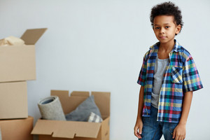 Little boy looking at camera on background of open boxes