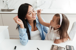 Little cute asian girl applying make up on her mothers face while sitting at the table at home