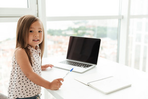 Little cute asian girl standing at home indoors near window using laptop computer and writing notes to notebook. Looking camera.