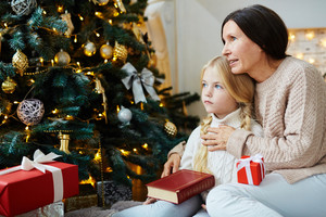Little girl and her grandmother sitting by decorated xmas tree