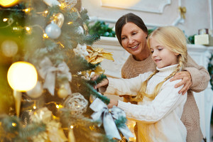 Little girl and her granny decorating xmas tree together