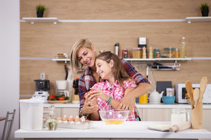 Little girl and her mother cooking together on the kitchen at home. Kitchen helper.