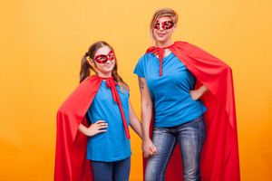 Little girl and mother dressed like superheros holding hands and smiling to the camera over yellow background. Super powers. Happy kid.