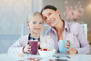 Little girl and senior woman with tea or coffee looking at camera