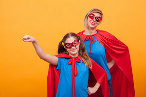 Little girl dressed like superheros holding her fist up in the air with her mother over eyellow background. Mother and daughter with red cape and maks.
