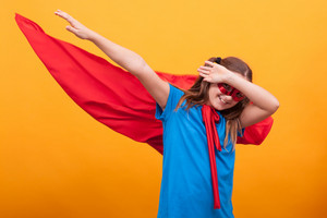 Little girl in red cape plays superhero in studio over yellow background. Happy childhood. Pretending to be superhero.