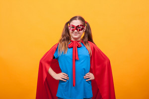 Little girl in super hero costume ready to save the world from bad guys over yellow background. Happy kid. Playing superhero.