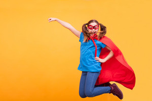 Little girl in superhero costume jumping in the air over yellow background. . Pure happiness. Freedome. Joy.