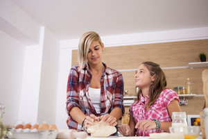 Little girl learning from her mother how to cook. Growing up.