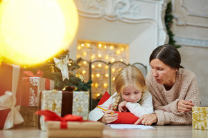 Little girl listening to her grandmother explaining how to write letter to Santa Claus