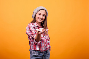Little girl playin with toy plane in studio on yellow background. Traveler young girl
