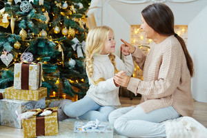 Little girl playing with her grandmother by decorated xmas tree