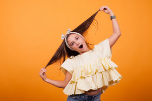 Little girl playing with her hair on a photoshoot in studio on yellow background. Happy girl.