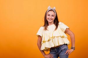 Little girl smiling on yellow background in studio. Happy kid,.