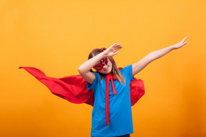 Little girl wearing superman costume ready to fly off in studio over yellow background. Flying off to catch the villains. Happy kid.