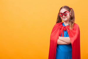Little girl wearing superman costume smiling to the camera over yellow background. Happy kid. Red mask.