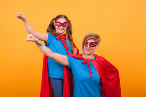 Little girl with her mother dressed like heroins holding their fists in the air and looking at the camera over yellow background. Superheros costume.
