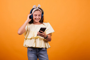 Little girl with yellow t-shirt listening music from her phone and headset. Joyfull gil