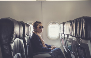 lonely asian woman sitting beside plane window use for traveling theme