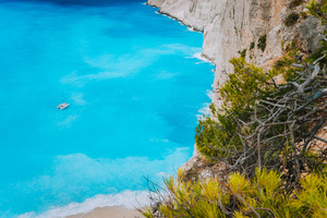 Lonely catamaran yacht in blue bay of Navagio beach. Azure turquoise sea water pattern near paradise sandy beach. Famous tourist visiting landmark on Zakynthos island, Greece