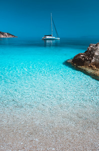 Lonely white sailing catamaran boat drift on calm sea surface. Pure azure clean blue lagoon with shallow water and pebble beach. Some brown rock stones in foreground