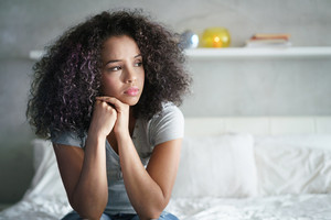 Lonely young latina woman sitting on bed. Depressed hispanic girl at home, looking away with sad expression.