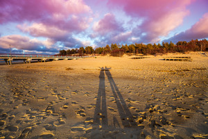 Long shadows of man and woman on the beach at sunset