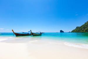 Longtail Boats Moored At Aonang Beach Against Blue Sky