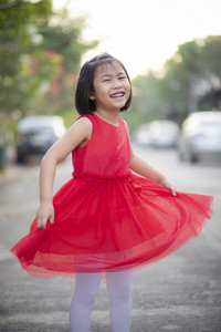 lovely asian girl wearing red skirt dress moving with happiness face outdoor