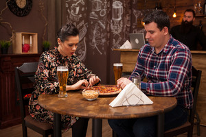 Lovely couple in new pub enjoying their beer. Hipster pub.