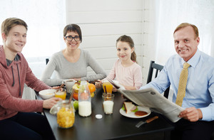 Lovely family of four looking at camera with wide smiles while having healthy breakfast at home, waist-up portrait