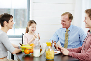 Lovely family of four sitting around dining table and enjoying healthy breakfast, cute little girl drinking milk from glass