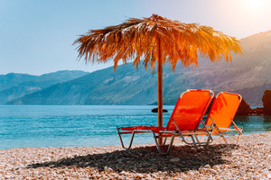 Lovely isolated beach and sunbeds under straw umbrella at warm sunset light