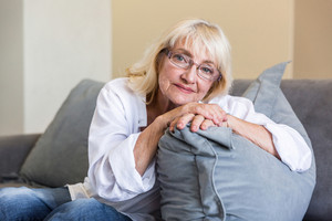 Lovely senior woman in eyeglasses leaning on a pillow while sitting on a couch in a living room