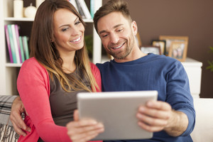 Loving couple using digital tablet at home