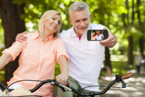 Loving mature couple taking selfie by mobile phone